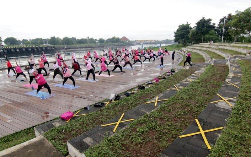 Warga melakukan gerakan yoga di Pulau Wangi, Pantai Boom, Banyuwangi, Jawa Timur, Minggu (6/12/2020). - Antara/Budi Candra Setya.