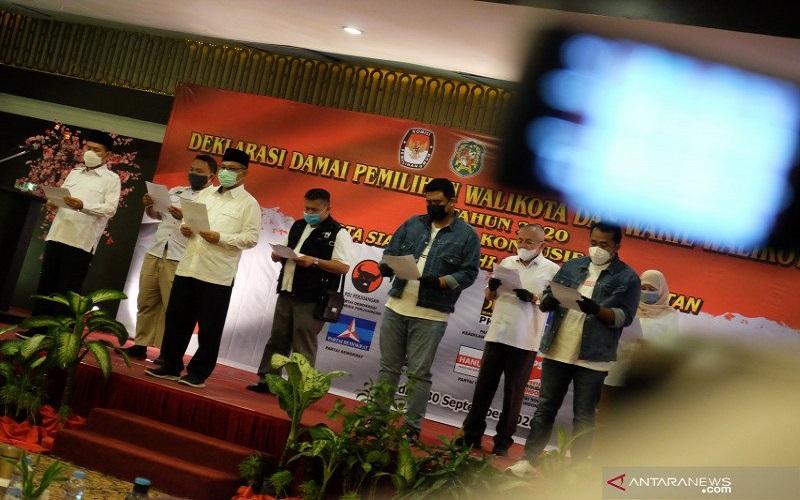 Pasangan calon Wali Kota-Wakil Wali Kota Medan nomor urut satu Akhyar Nasution (ketiga kiri) Salman Alfarisi (kiri) dan nomor urut dua Bobby Nasution (keempat kanan) Aulia Rahman (kedua kanan) didampingi masing-masing tim kampanye membaca ikrar Deklarasi Damai Pilkada, di Medan, Sumatera Utara, Rabu (30/9 - 2020). Deklarasi tersebut berisi komitmen bersama diantaranya saling menjaga kondusifitas selama proses tahapan Pilkada serta menerapkan protokol kesehatan guna mencegah penyebaran COVID/19. ANTARA FOTO