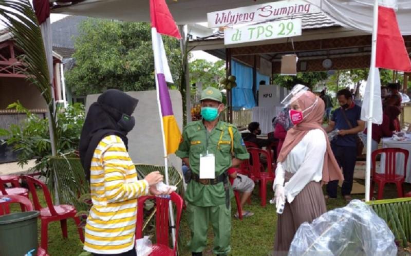 Satu orang relawan kesehatan ditempatkan di TPS selama Pilkada Cianjur, Jawa Barat, untuk melakukan pengecekan suhu pemilih yang datang dn tenaga kesehatan ditempatkan di kecamatan sebagai upaya penanganan cepat ketika dibutuhan selama pilkada - Antara