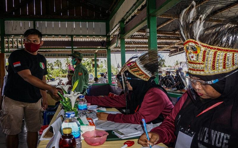 Sejumlah petugas KPPS mengenakan mahkota ciri khas Papua di Tempat Pemungutan Suara (TPS) 01, Kampung Wiantre (Arso V), Distrik Skanto, Kabupaten Keerom, Papua, Rabu (9/12/2020). Menurut Ketua KPU Keerom Melianus Gobay sebanyak 54.490 Daftar Pemilih Tetap (DPT) tersebar di 185 TPS di Kabupaten Keerom. - Antara/Indrayadi TH.