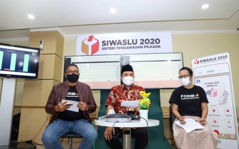 Anggota Bawaslu Fritz Edward Siregar (kiri) bersama Anggota Bawaslu M. Afifuddin (tengah) merilis hasil pengawasan pemungutan dan penghitungan suara di Media Center Bawaslu Jakarta, Rabu (9/12/2020). - Bawaslu