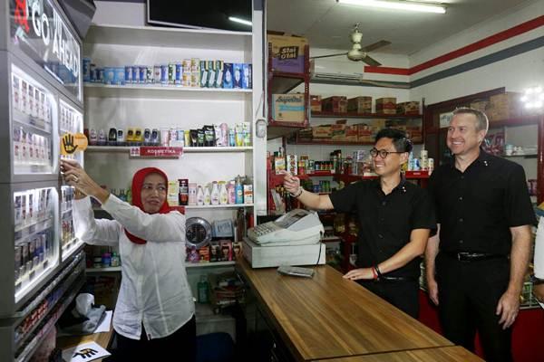 Pemilik Toko Mm - Qia Hj Tachlis (dari kiri), Direktur Sampoerna Ivan Cahyadi dan Director Corporate Affairs PT HM Sampoerna Tbk Troy Modlin disela acara penerapan program pencegahan akses pembelian rokok oleh anak-anak (PAPRA) di Jakarta. Kamis (14/12). - JIBI/Nurul Hidayat