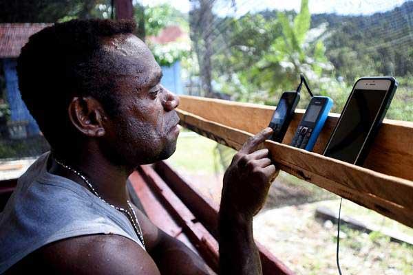 Warga menerima panggilan masuk melalui telepon genggamnya di pelosok Mosairo, Nabire, Papua, Selasa (11/7). - ANTARA/Indrayadi TH