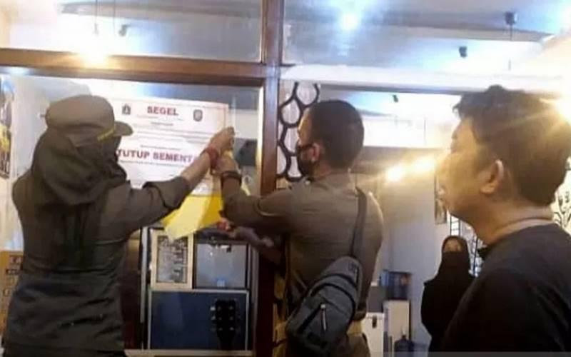 Petugas Satpol PP Pulogadung menyegel salah satu kafe di Jalan Raya Pemuda, Jakarta Timur sebab beropersional melebihi jam yang ditentukan serta melanggar protokol kesehatan, Minggu (15/11/2020). - Antara\r\n