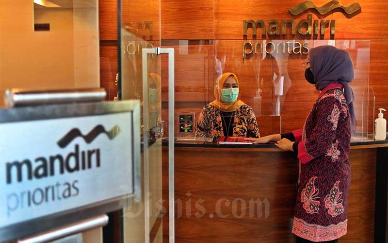 Karyawan melayani nasabah Prioritas di Cabang Mandiri Prioritas Plaza Mandiri, Jakarta, Rabu (7/10/2020).  Bisnis - Eusebio Chrysnamurti