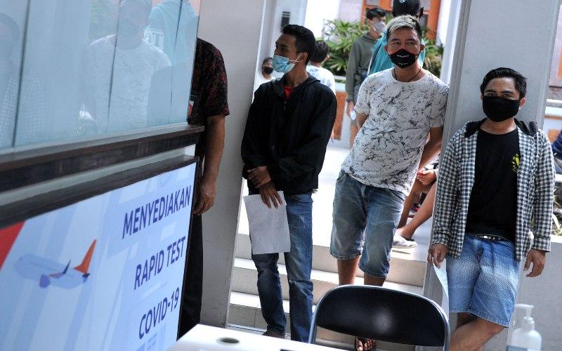 Warga antre saat akan melakukan tes cepat (rapid test) COVID-19, di area Terminal Domestik Bandara Internasional I Gusti Ngurah Rai, Badung, Bali, Jumat (18/12/2020). - ANTARA FOTO/Fikri Yusuf