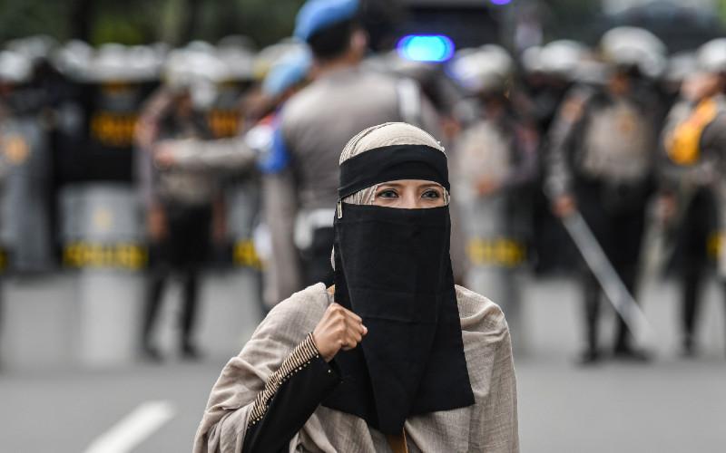 Seorang pengunjuk rasa aksi demonstrasi 1812 mengepalkan tangan saat membubarkan diri, di kawasan Medan Merdeka Selatan, Jakarta, Jumat (18/12/2020). Kepolisian membubarkan paksa massa aksi demonstrasi dikarenakan angka penyebaran Covid-19 masih tinggi di wilayah Jakarta.  - ANTARA FOTO