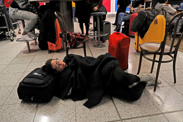 Seorang penumpang berbaring untuk beristirahat di Terminal Selatan di Bandara Gatwick, London, setelah drone yang terbang ilegal di sekitar bandara memaksa pihak bandara menunda penerbangan dari dan ke bandara tersebut, Kamis (20/12/2018). - Reuters/Peter Nicholls