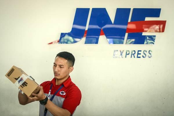 Pekerja membungkus paket di Kantor Cabang Utama PT Jalur Nugraha Ekakurir (JNE), Bandung. - ANTARA/Raisan Al Farisi