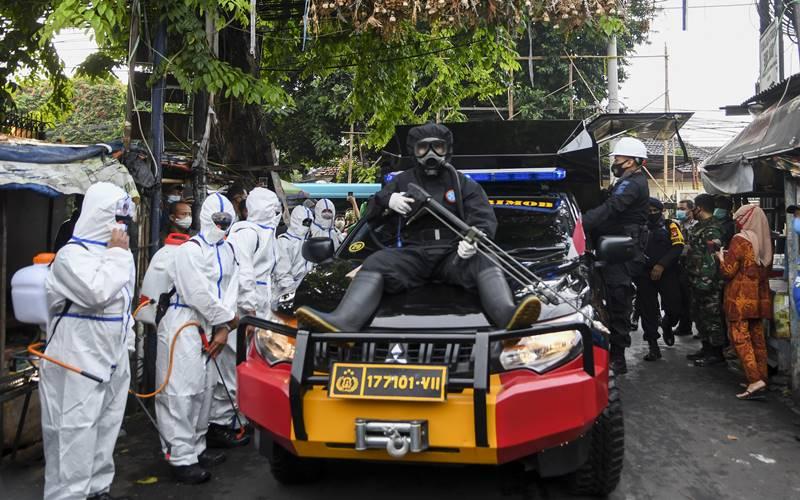 Anggota kepolisian dengan mengenakan hazmat bersiap menyemprotkan cairan disinfektan di kawasan Petamburan III, Jakarta Pusat, Minggu (22/11/2020).  - Antara