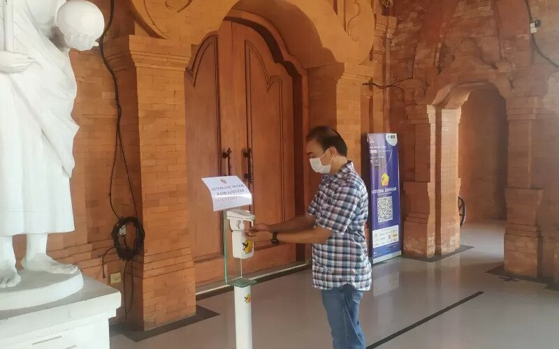 Seorang pengurus Gereja Katedral menggunakan hand sanitizer sebelum memasuki dalam Gereja di Denpasar, Bali, Kamis (24/12/2020). - Antara/Ayu Khania Pranisitha