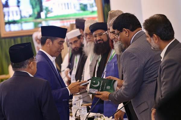 Presiden Joko Widodo (kedua kiri) didampingi Wakil Presiden Jusuf Kalla (kiri) menerima buku tentang Pakistan ketika menyalami sejumlah ulama yang mengikuti pertemuan trilateral ulama Afganistan, Indonesia dan Pakistan di Istana Bogor, Jawa Barat, Jumat (11/5/2018). - ANTARA/Wahyu Putro A