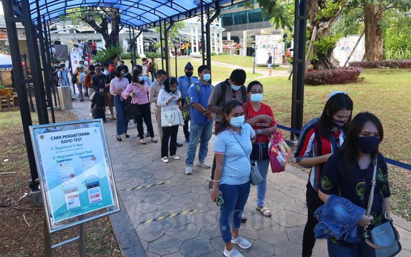 Antrean calon penumpang yang akan melakukan tes Covid-19 di Farmalab Terminal 3 Bandara Soekarno-Hatta pada Jumat (18/12/2020). Antrean mulai terlihat sejak pukul 11.00 WIB./Bisnis - Eusebio Chrysnamurti