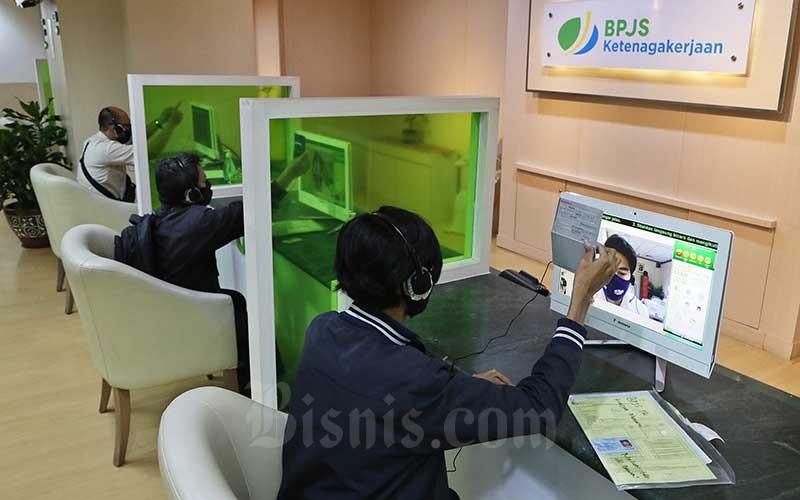 Ilustrasi - Peserta BP Jamsostek berkomunikasi dengan petugas pelayanan saat mengurus klaim melalui layar monitor dan tanpa kontak langsung di Kantor Cabang BP Jamsostek di Menara Jamsostek, Jakarta, Jumat (10/7/2020). Bisnis - Eusebio Chrysnamurti