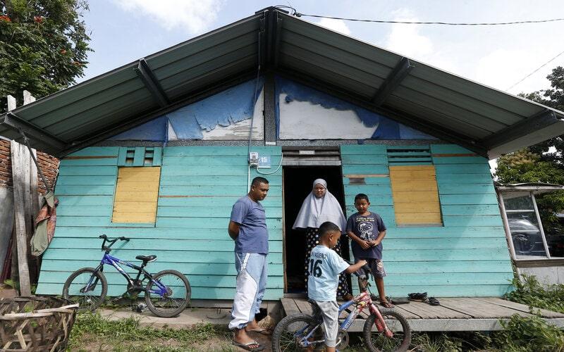 Korban tsunami Aceh 26 Desember 2004 Rian Aldiansyah (kiri) bersama keluarga berada di depan rumah sementera (shelter) yang ditempatinya di Gampong Lampaseh Kota, Banda Aceh, Aceh, Jumat (25/12/2020). Rian Aldiansyah yang kehilangan ibu dan neneknya saat bencana tsunami telah menempati rumah shelter bersama keluarganya selama 16 tahun dan berharap mendapat bantuan dari berbagai pihak untuk membangun kediaman yang layak. - Antara/Irwansyah Putra.