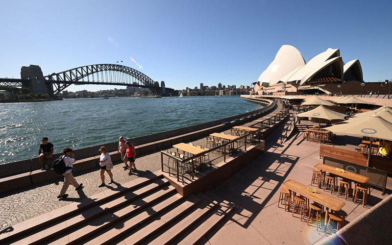 Sejumlah orang pada 20 Maret 2020 berjalan di Circular Quay di Sydney melewati kafe-kafe yang kosong akibat lockdown yang diberlakukan untuk membendung penularan virus corona jenis Covid-19. - Bloomberg