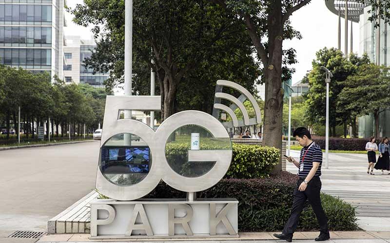Warga menggunakan smartphone berjalan melewati papan Taman 5G di markas Huawei Technologies Co. di Shenzhen, China, Rabu(22/5/2020).Bloomberg - Qilai Shen