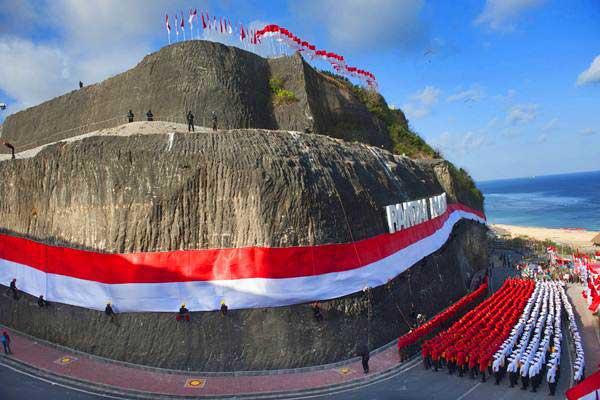Ilustrasi - Anggota Brimob Polda Bali dan Basarnas mengibarkan bendera Merah Putih di dinding tebing Pantai Pandawa, Badung, Bali, Senin (14/8). - Antara/Nyoman Budhiana