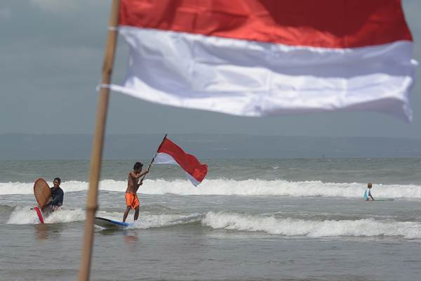 Sejumlah peselancar yang terabung dalam komunitas anak pantai mengibarkan bendera Merah Putih, di Pantai Berawa, Badung, Bali, Selasa (15/8). Kegiatan tersebut untuk menghormati para pahlawan bangsa sekaligus memperingati HUT ke-72 Kemerdekaan Republik Indonesia. ANTARA FOTO - Wira Suryantala