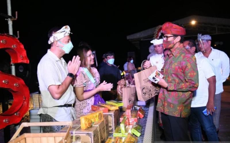 Menteri Pariwisata dan Ekonomi Kreatif (Menparekraf) Sandiaga Uno membeli produk-produk ekonomi kreatif asli Bali disela dialog santai dengan perwakilan pelaku usaha pariwisata dan ekonomi kreatif yang digelar di Tanjung Benoa, Bali, Minggu (27/12/2020). (ANTARA - HO/Kemenparekraf)