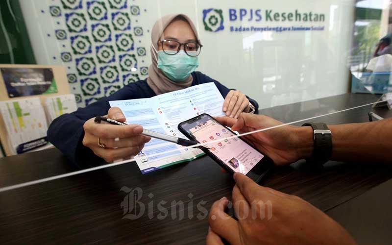Petugas menjelaskan kepada peserta tentang fitur-fitur yang ada di aplikasi Mobile JKN di Kantor BPJS Kesehatan Cabang Bandung, Jawa Barat, Kamis (13/8/2020). Bisnis - Rachman