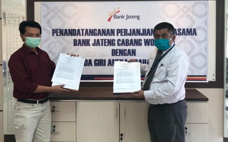 Wakil Pemimpin Bank Jateng Cabang Wonogiri Gunawan Suprapto (kanan) dan Direktur Perusda Giri Aneka Usaha Wonogiri Suharsono seusai menandatangani perjanjian kerja sama mengenai layanan pembayaran gaji dan pemberian fasilitas kredit bagi para pegawai.
