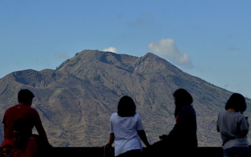 Wisatawan domestik menikmati pemandangan Gunung Batur dari kawasan wisata Kintamani, Bangli, Bali, Rabu (28/10/2020). Sejumlah objek wisata di Pulau Dewata mulai dikunjungi wisatawan domestik dari berbagai daerah yang memanfaatkan masa cuti bersama dan libur panjang Maulid Nabi Muhammad SAW. ANTARA FOTO - Fikri Yusuf