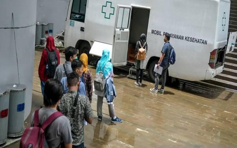 Sejumlah calon relawan mengantre untuk melakukan tes kesehatan di Komplek Wisma Atlet di Kemayoran, Jakarta, Minggu (22/3/2020). - Antara