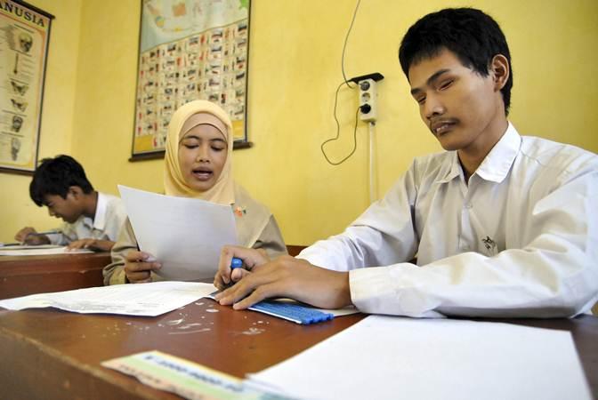 Guru membantu siswa kelas 6 SDLB penyandang disabilitas tunanetra mengerjakan soal Pendidikan Agama Islam saat Ujian Sekolah Berstandar Nasional (USBN) SD di SLB ABCD Sejahtera, Kelurahan Loji, Kota Bogor, Jawa Barat, Senin (22/4/2019). - ANTARA/Arif Firmansyah
