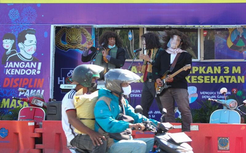 Polisi berpakaian sipil bermain musik saat sosialisasi penerapan protokol kesehatan di depan pos pengamanan di Surabaya, Jawa Timur, Rabu (23/12/2020). Sosialisasi dengan menyisipkan protokol kesehatan yaitu Memakai Masker, Menjaga Jarak, Mencuci Tangan dalam lagu yang dinyanyikannya itu bertujuan agar masyarakat tetap terus menerapkan protokol kesehatan pencegahan penyebaran Covid-19 dalam kesehariannya. - Antara/Didik Suhartono.