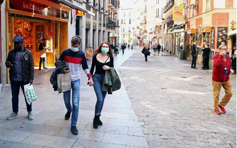 Sepasang suami istri memakai masker pelindung saat berjalan di jalan Postas yang luar biasa sepi di pusat kota Madrid, Spanyol, 13 Maret 2020. / REUTERS