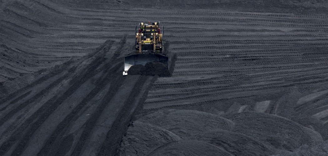 Alat berat membersihkan area penimbunan batu bara. -  Bloomberg / Nicolo Filippo Rosso