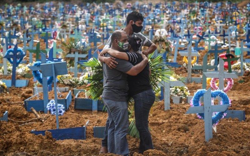 Kerabat korban Covid-19 berkabung dalam pemakaman massal korban virus corona di Manaus, Brasil pada 19 Mei. -  Andre Coelho/Bloomberg via Getty Images Amerika Selatan