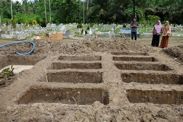 Warga melihat liang kubur yang telah disiapkan untuk pemakaman korban kebakaran pabrik korek api gas (mancis) di perkuburan muslim, Desa Sambirejo, Langkat, Sumatera Utara, Minggu (23/6/2019).  - Antara