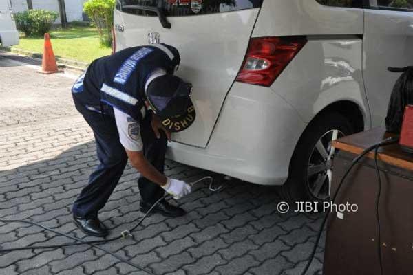 Petugas melakukan uji emisi kendaraan bermotor.  - Jibi Foto