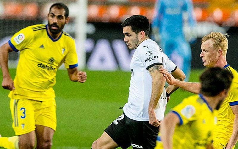 Penyerang Valencia Maxi Gomez (putih) mencoba menembus pertahanan rapat Cadiz. - Twitter@valenciacf