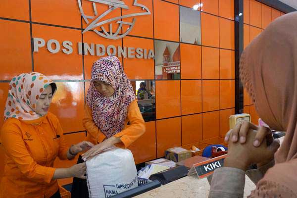 Petugas melayani jasa pengiriman paket barang di PT Pos Indonesia, Tulungagung, Jawa Timur, Selasa (13/6). - Antara/Destyan Sujarwoko