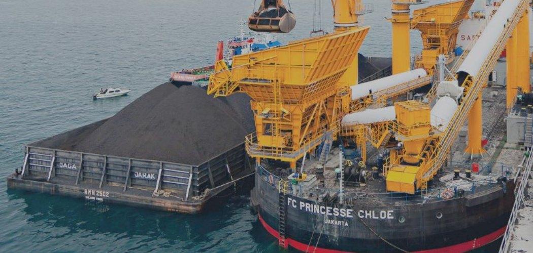 Aktivitas pemindahan muatan batu bara dari tongkang ke kapal induk dengan floating crane. - indikaenergy.co.id