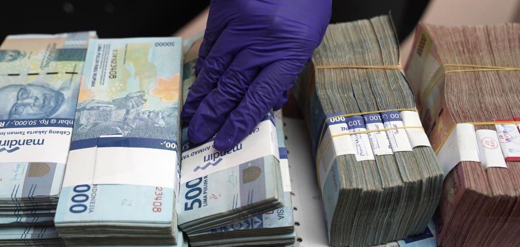 Pegawai money changer merapikan uang nominal Rp50.000 dan Rp100.000 di Jakarta, Indonesia, Selasa (18/8/2020). - Bloomberg/Dimas Ardian