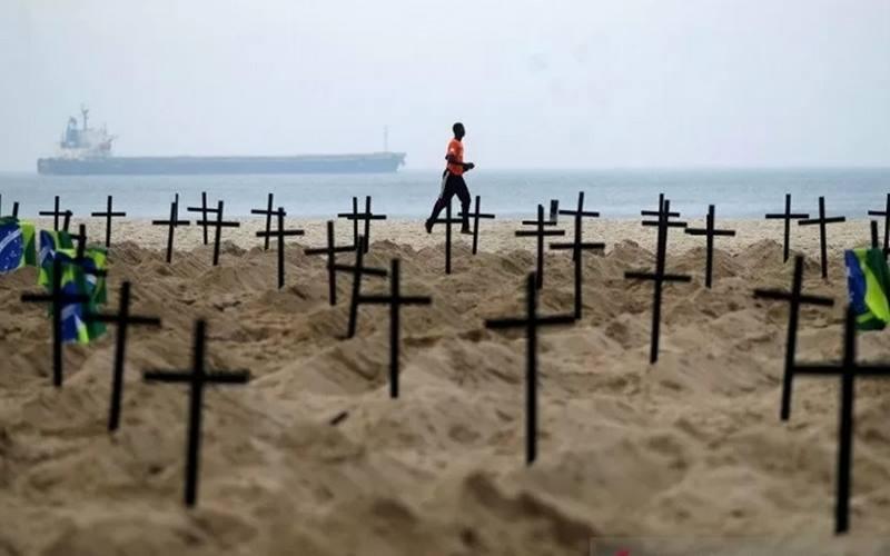 Seorang pria berlari melewati ratusan makam yang digali oleh aktivis LSM Rio de Paz di Pantai Copacabana, menyimbolkan warga yang meninggal dunia akibat penyakit  Covid-19 di Rio de Janeiro, Brasil, Kamis (11/6/2020). - Antara/Reuters