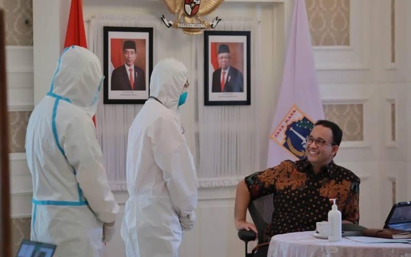 Gubernur DKI Jakarta Anies Baswedan dua dua tenaga kesehatan mengenakan alat pelindung diri (APD). Anies psoitif Covid-19 dan dalam masa isolasi mandiri. JIBI - Bisnis/Nancy Junita @kawalCOVID19