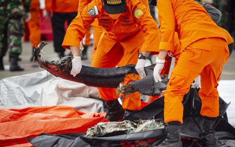 Petugas Basarnas pada Minggu (10/1/2021) di Dermaga JICT, Tanjung Priok, Jakarta Utara, memeriksa temuan bagian dari pesawat Sriwijaya Air SJ182 rute Jakarta-Pontianak yang jatuh di perairan Pulau Seribu pada Sabtu (9/1/2021). Tim penyelam Kopaska TNI AL menemukan sejumlah serpihan dari pesawat dan pakaian yang diduga milik penumpang di lokasi jatuhnya pesawat tersebut./Antara - Dhemas Reviyanto