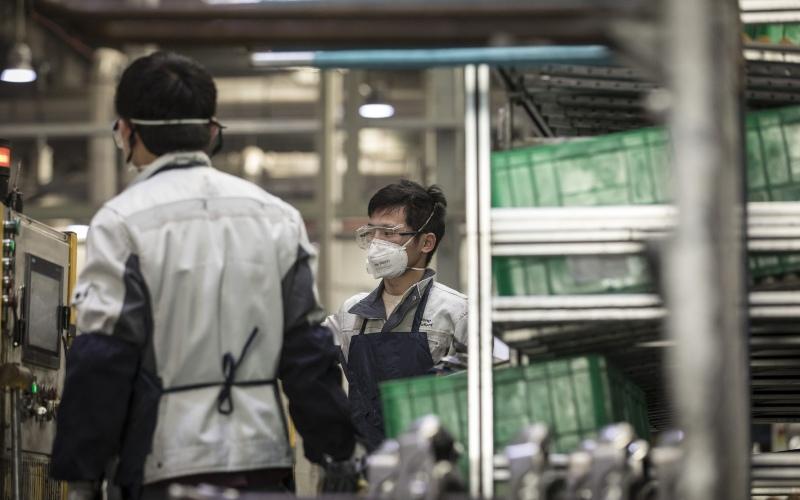 Pekerja mengenakan masker di pabrik milik Yanfeng Adient Seating Co. di Shanghai, China, Senin (24/2/2020). - Bloomberg/Qilai Shen