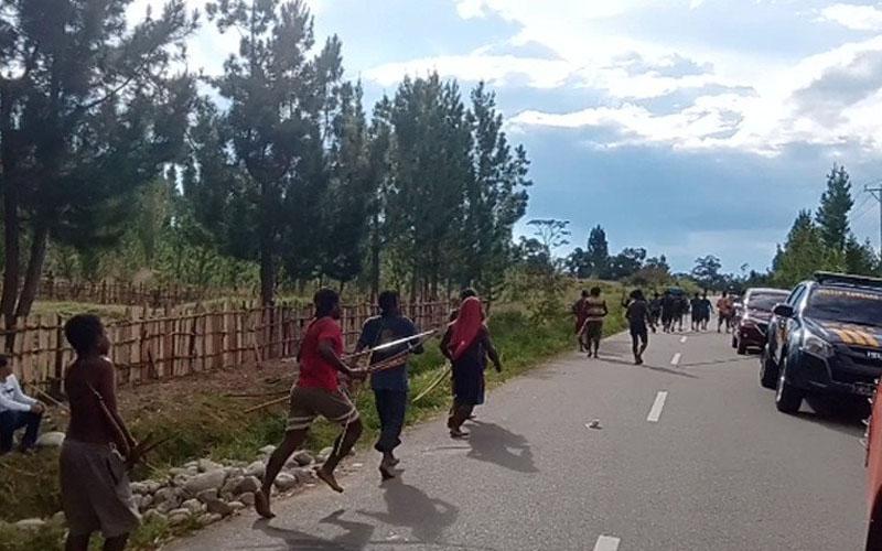 Warga yang terkesan tidak peduli keberadaan polisi dan terus berlari ke arah tempat yang diduga akan datang kelompok lawan dalam perang antara kampung di Kabupaten Jayawijaya, Papua, Sabtu 12 September 2020. - Antara/Marius Frisson Yewun