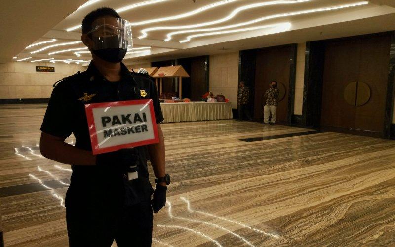 Salah satu karyawan di Hotel Claro Makassar bertugas mengingatkan pengunjung dengan menggunakan papan bicara dalam menggencarkan gerakan 3M, memakai masker, menjaga jarak, dan mencuci tangan.  - Bisnis/Andini Ristyaningrum.