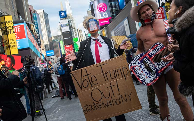 Seorang pengunjuk rasa berpakaian seperti Presiden AS Donald Trump membawa papan bertulisan Vote Him Out!  di Times Square selama pemilihan Presiden 2020 di New York, AS, Selasa (3/11/2020). Bloomberg - Jeenah Moon