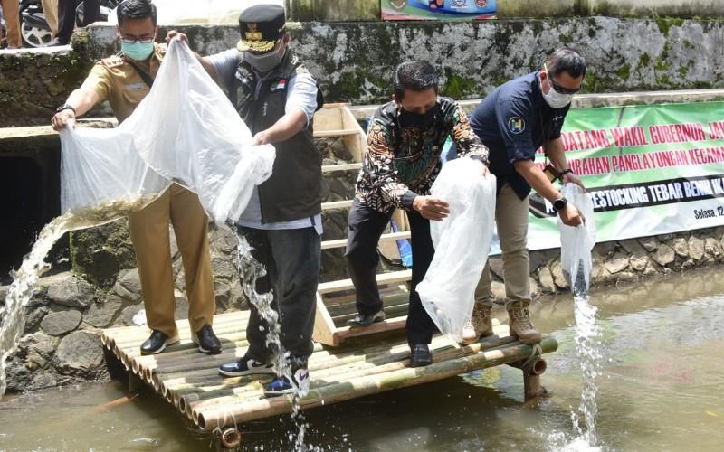 Wakil Gubernur Jawa Barat Uu Ruzhanul Ulum (kedua kiri) menebarkan puluhan ribu benih ikan tawes, nilem, dan nila, di Sungai Cidukuh dan Cimulu, Kota Tasikmalaya