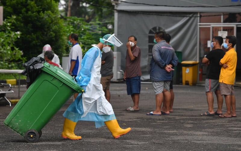 Petugas kebersihan dengan pakaian pelindung diri melintas di samping pasien Covid-19 yang mengantre memeriksa kesehatan di Rumah Sakit Lapangan Kogabwilhan II Jalan Indrapura, Surabaya, Jawa Timur, Selasa (12/1/2021). Berdasarkan data Satuan Tugas Penanganan Covid-19 pada Selasa (12/1) kasus positif Covid-19 bertambah 10.047 orang menjadi 846.765 orang, sementara kasus pasien sembuh bertambah 7.068 orang menjadi 695.645 orang. - Antara/Zabur Karuru.