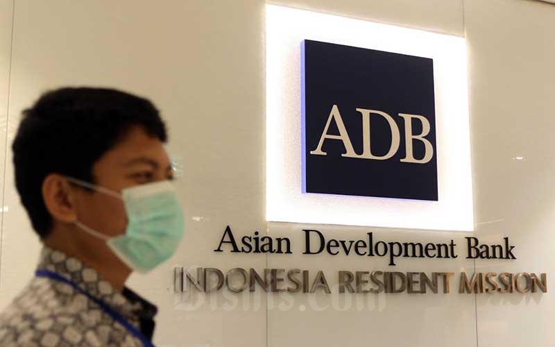 Karyawan berada di dekat logo Asian Development Bank Indonesia di Jakarta, Rabu (8/4/2020). Bisnis - Eusebio Chrysnamurti