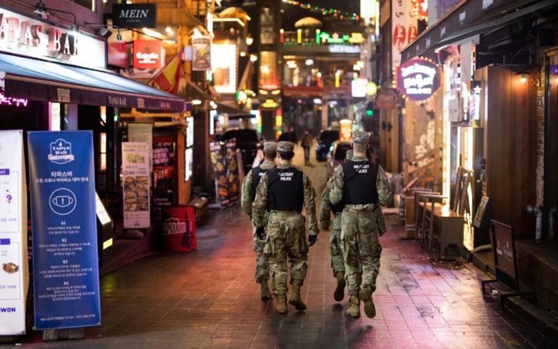 Polisi militer Angkatan Darat AS berpatroli di jalan di Itaewon, Seoul, Korea Selatan, pada Sabtu (9/5/2020) malam, ketika gelombang kedua infeksi virus corona berpotensi muncul, terkait dengan aktivitas kelab malam malam. - Bloomberg